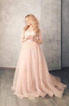 Абсолютная нежность воплощена в платье Vesta. Выполненное в оттенке розовый кварц, оно выгодно подчеркнет любую невесту. Флер загадочности придает плетеное кружево по всему корсету и рукавам, а маленькие детали- пуговки-кристаллы и аккуратный поясок с бантиком добавляют изыска в образ.