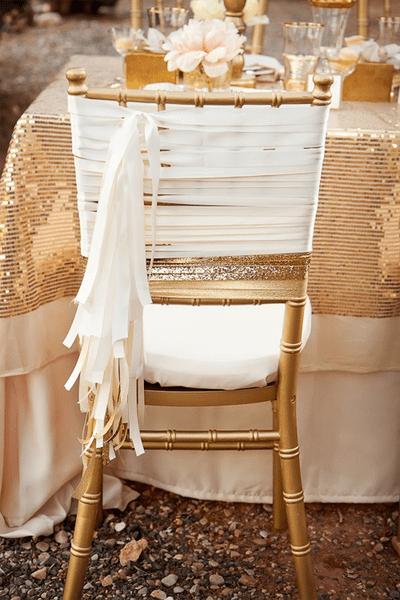 Hochzeits-Dekoration: Goldener Stuhl mit weißen Bändern, Foto: AKStudio & Design