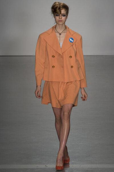 Conjunto laranja com blazer e saia.