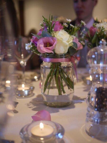 Centro de mesa de boda con botellas de cristal con agua