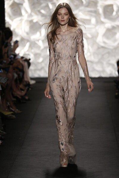 L'abito in tinte nude e velo illusion è ricoperto da ramages preziosi.
