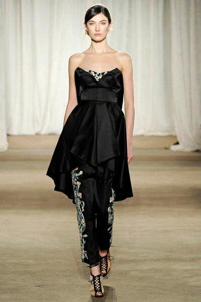 Vestido de fiesta corto, con acabado asimétrico y escote strapless sobre pamtalones rectos en color negro con estampados en los costados