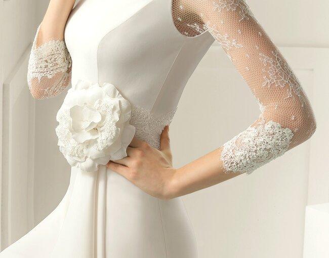 Robe de mariée avec manches en dentelle et fleur à la taille.