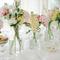 Arreglos de mesa para bdoas elegantes con envases de cristal y flores en colores blanco, rosa y amarillo pálido