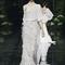 Vestido de novia con escote asimétrico, manga holgada, falda amplia con detalles de flequillos y cauda mediana