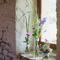 Arreglos de mesa para recepción de boda con flores coloridas en tonos rosa y morado y contraste con hojas verdes