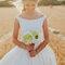 Novia con vestido de cuello barco y bouquet frente a un campo de trigo.