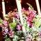 Detalle de centro de mesa compuesto de flores muy coloridas y velas.