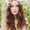 Noiva com cabelo encaracolado em ondas largas e tiara de motivos florais em tons de branco.