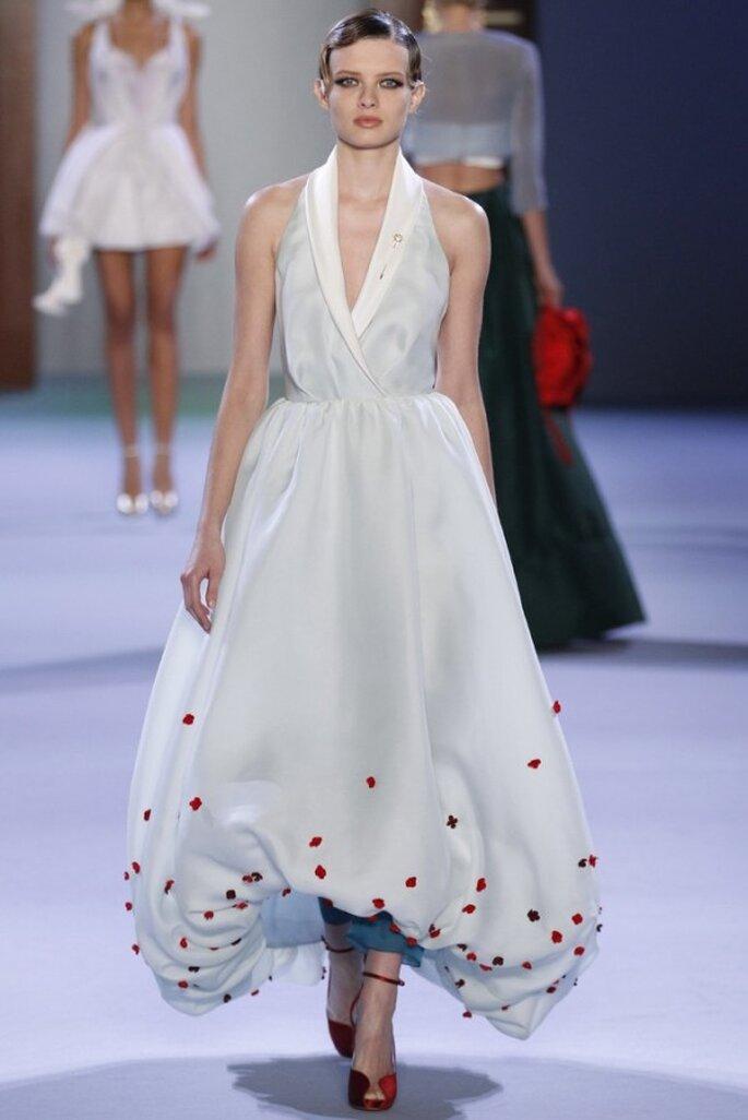 Vestido de novia alta costura con falda high low de globo, detalles en color rojo y cuello halter - Foto Ulyana Sergeenko