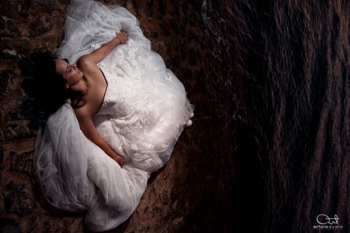 Novia con su vestido acostada en la arena para una sesion trash the dress - Foto: Arturo Ayala