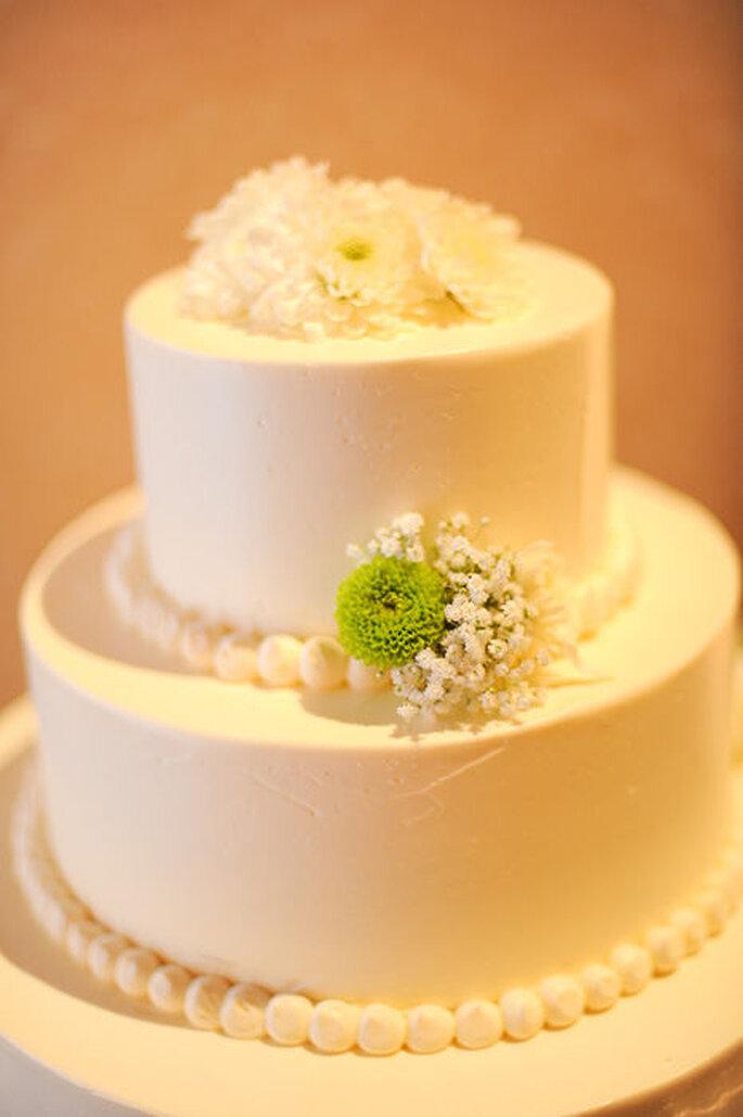 Pastel de boda blanco, redondo a 2 niveles, adornado con flores y detalles verde
