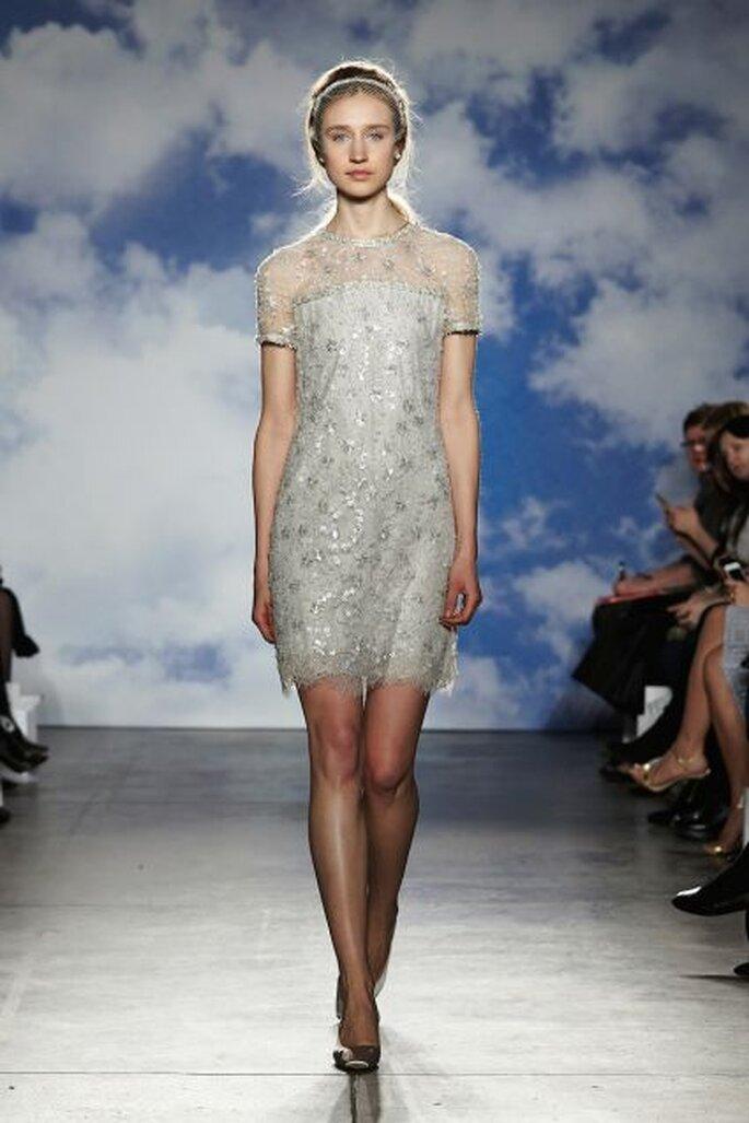Vestido de novia corto. Las transparencia en el escote y las mangas se complementan con los brodados brillantes. Diseño de Jenny Packham 2015