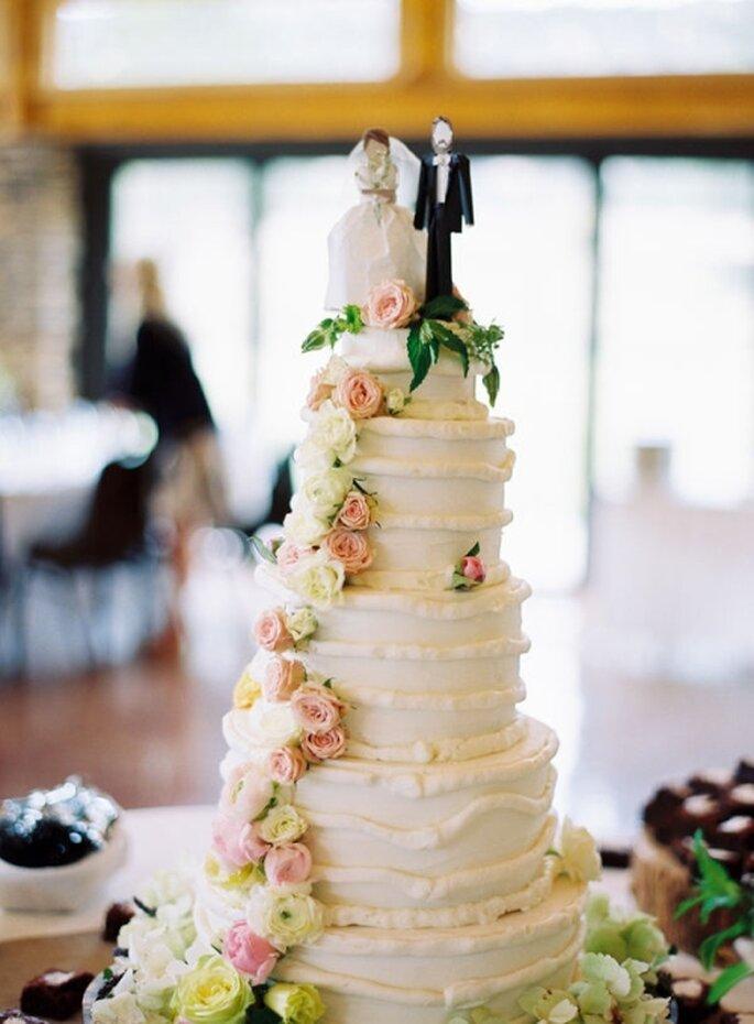 Pastel de boda alto, decorado con flores comestibles en línea vertical y personajes