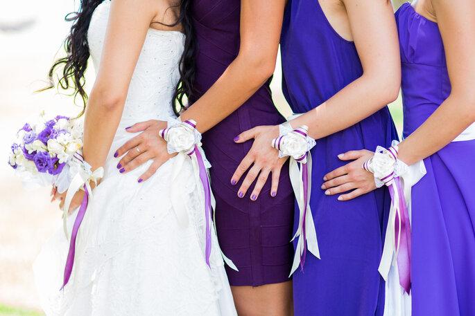 Damas de honor con vestidos en tonos violeta. Foto vía Shutterstock