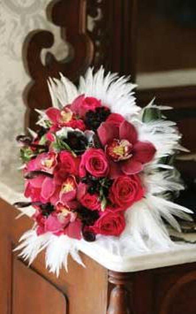 Orchidee e rose in toni porpora con bacche circondate da piume
