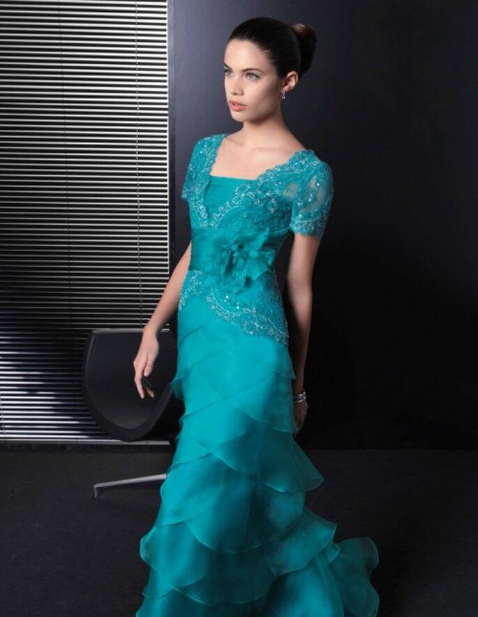 Vestido de fiesta en color verde esmeralda con mangas cortas, encaje, detalle de flor en relieve en el costado y falda con superposición de volúmenes - Foto Rosa Clará