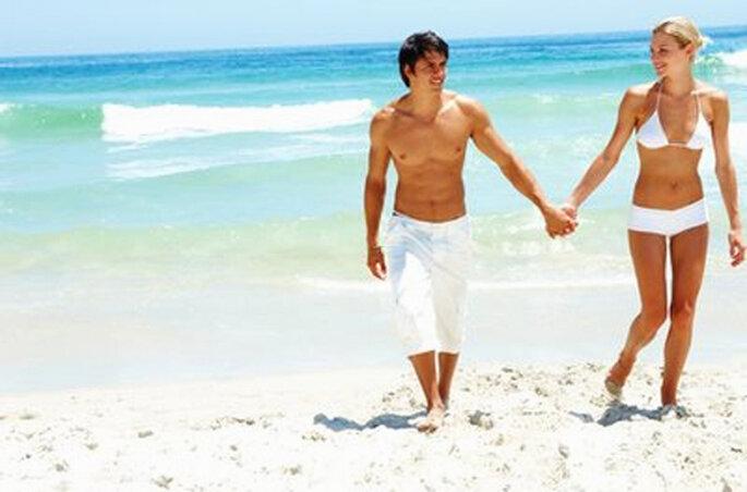 Pareja de recien casados caminando por la playa - Foto: Pixmac
