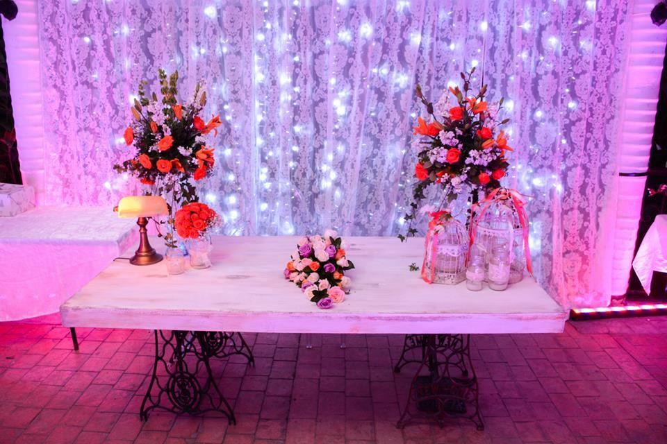 Mesa de Novios estilo vintage con base de maquinas decorada con arreglos florales, lampara y jaulas vintage .