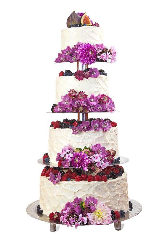 Vierstöckige Hochzeitstorte auf Etagere mit Buttercreme Struktur, frischen Blumen und Beeren