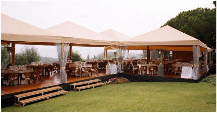Carpas para boda en color beige, con todo el interior tapizado con tela beige, donde no se aprecia la estructura de la carpa, puesto que está perfectamente recubierta. La carpa tiene tarima de madera y en su perímetro tiene cortinas transparentes.
