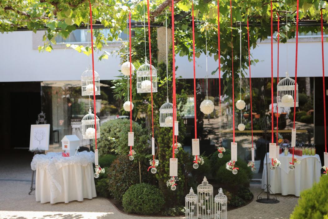As fitas suspensas com os cartões, os pequenos arranjos florais nas pontas e as gaiolas ajudam ao ambiente e completam o