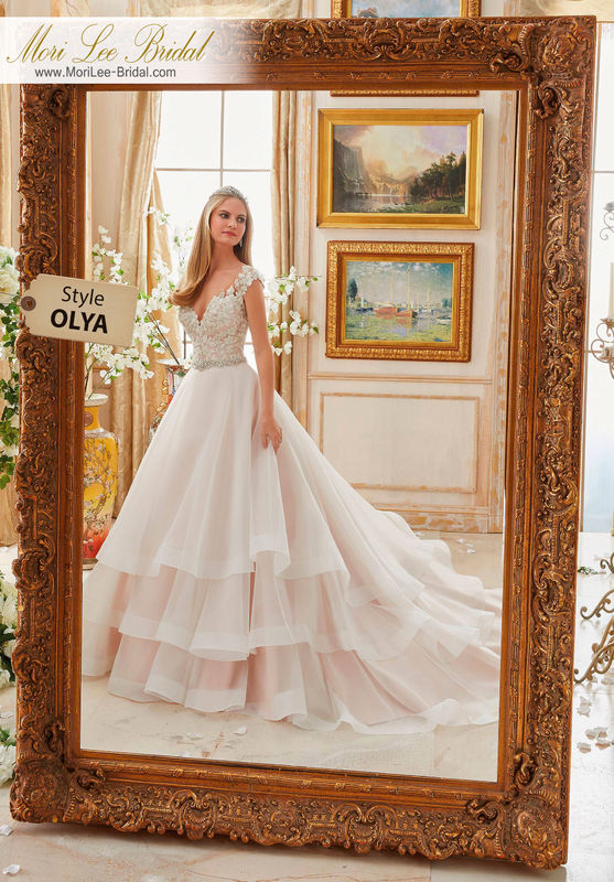 Dress Style OLYA  VINTAGE EMBROIDERY TRIMMED WITH CRYSTAL MOONSTONE BEADING ON TIERED ORGANZA BALL GOWN  Available in Three Lengths: 55 , 58 , 61 . Colors Available: White/Silver, Ivory/Silver, Ivory/Blush/Silver