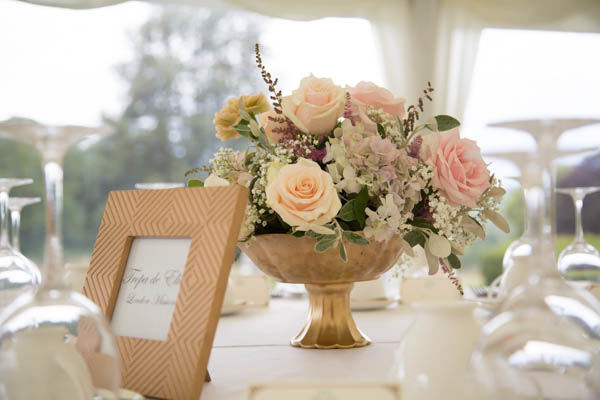 Low level table decoration. Gold coloured rose bowl filled with vintage peachy pinks