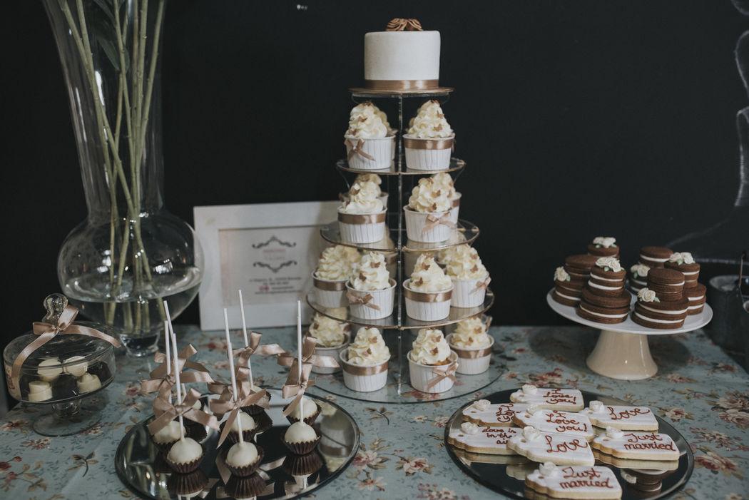 Mesa de postres con torre de cupcakes y mini tarta nupcial, galletas decoradas, cakepops, galletas de chocolate en forma de tarta y bombones.