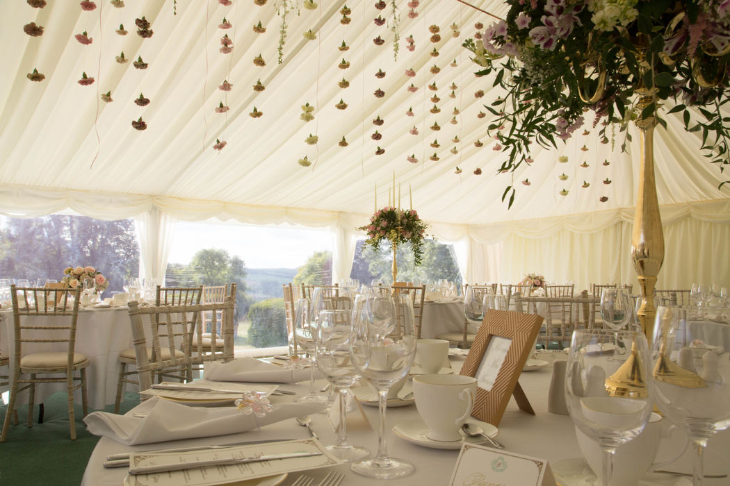 Marquee flowers. Fresh flower curtain and gold coloured table candelabra displays
