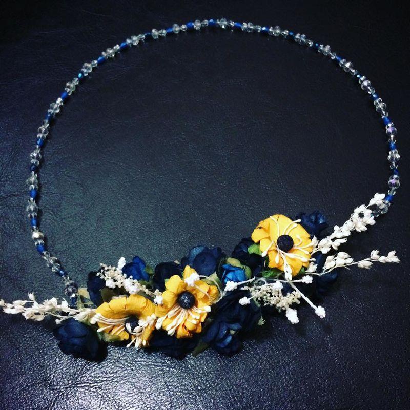 Corona de cristales transparentes y azules que son el complemento perfecto para un ramillete de flores azules y girasoles acompañados de pistilos y ramitas color blanco.