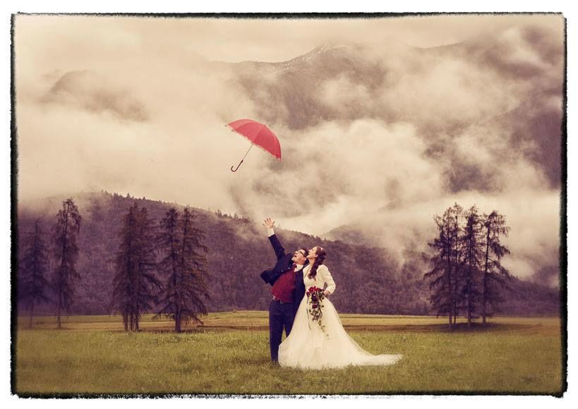 Foto: Brautpaar mit einem roten Regenschirm