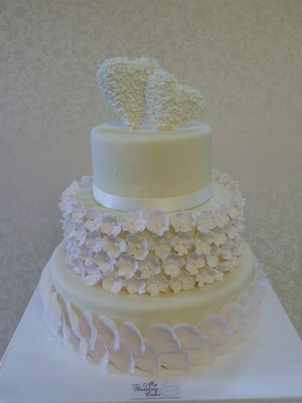 Vintage Hochzeitstorte mit pastellfarbenen Zuckerblüten , Topper mit Blütenherz aus Zuckerblüten. Foto:Bruggers  My Weddingcake.ch