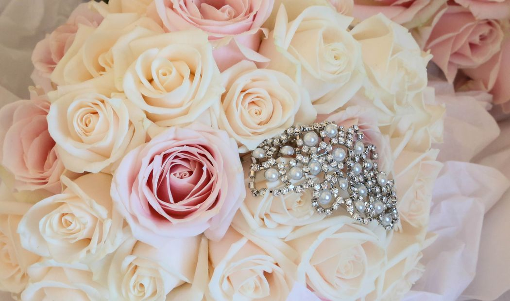 Bridal bouquet of ivory, champagne and soft pink roses complete with vintage brooch detail