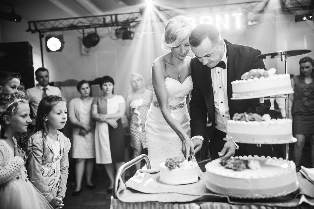 Para Młoda krojąca tort