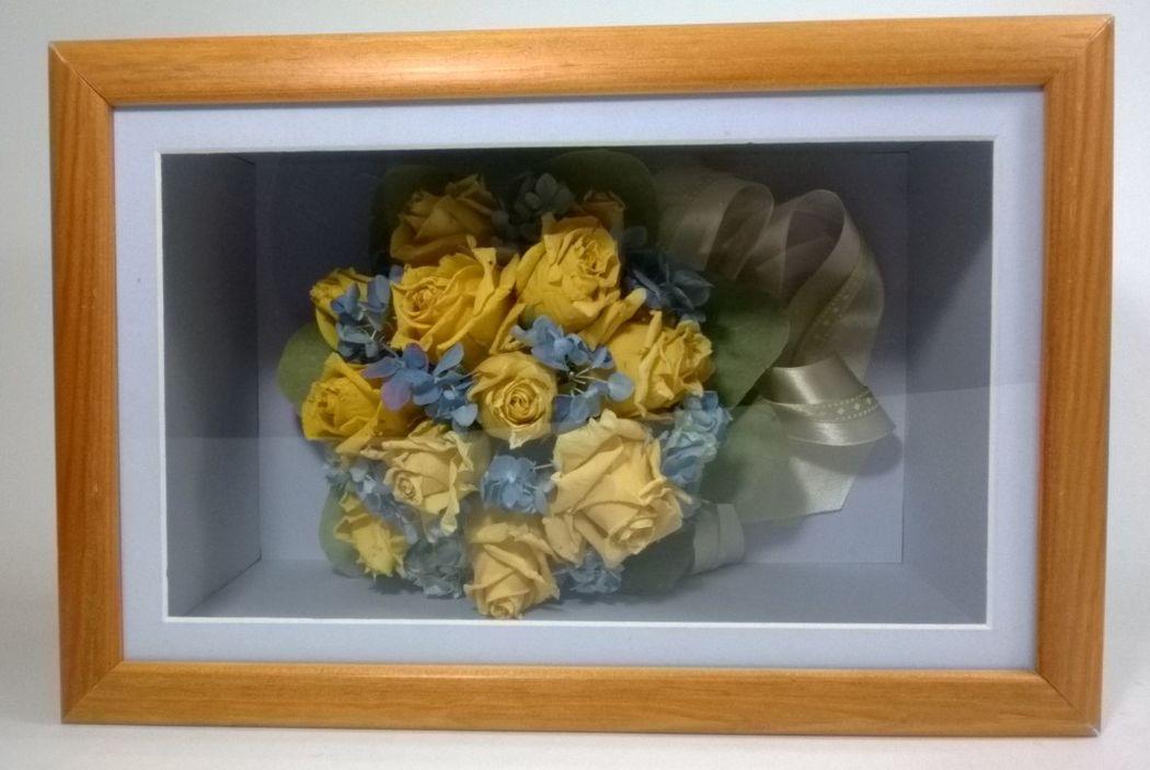 Bukiet z żółtych róż i błękitnych hortensji w drewnianej skrzynce.