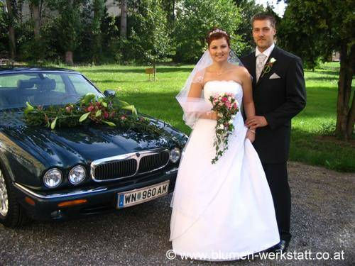Beispiel: Hochzeitspaar mit Brautstrauß und Autoschmuck, Foto: Blumenwerkstatt Klára Kwas.