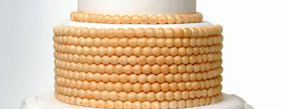 Tort Złoty. Niezwykle elegancki i oryginalny. Każde piętro to inny smak i dodatki.   Na samym dole mamy czekoladowy biszkopt przełożony kremem czekoladowym z dodatkiem wiśni moczonej w alkoholu, to połączenie zadowoli wszystkich miłośników czekolady. Piętro drugie to orzechowe blaty przełożone kremem z siekanymi orzechami włoskimi. Góra tortu ma delikatny waniliowy smak, który podkreślony został dodatkiem drobno krojonych brzoskwiń.  Polecam ten wyjątkowy tort który na pewno zadziwi naszych gości.