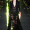 Longue robe en dentelle noire aux manches trois quart surmontée d'une élégante veste.