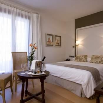 """Una mesa con un detalle de bienvenida, ambientes cuidados y el lujo de los detalles, son algunos de los aspectos que hacen única la  habitación que escojas para tu noche de bodas y que puedes encontrar en espacios como esta habitación del Parador de Puebla de Sanabria. Foto: <a href=""""http://zankyou.9nl.de/wdbk"""" target=""""_blank"""">Paradores</a><img src=""""http://ad.doubleclick.net/ad/N4022.1765593.ZANKYOU.COM/B7764770.4;sz=1x1"""" alt="""""""" width=""""1"""" border=""""0"""" /><img height='0' width='0' alt='' src='http://9nl.de/xyl3' />"""