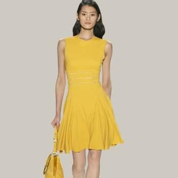 Abito corto con spalla larga e gonna plissettata color giallo. Elie Saab.