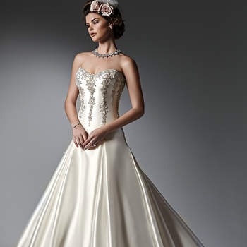 Dramatic and sophisticated, this Elodie Mikado, fitted A-line wedding dress features lines of metallic embroidered lace and Swarovski crystals adorning the bodice, and a full, pleated skirt with pockets. Finished with corset closure. <img height='0' width='0' alt='' src='http://ads.zankyou.com/mn8v' />