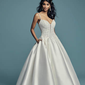 "<a href=""https://www.maggiesottero.com/maggie-sottero/dana/11464"">Maggie Sottero</a>  Delicate beaded motifs adorn the bodice of this Elodie Mikado princess wedding dress, drifting into a billowing ballgown skirt with pockets. Beaded spaghetti straps complete the illusion plunging sweetheart neckline. Finished with crystal buttons over zipper closure."