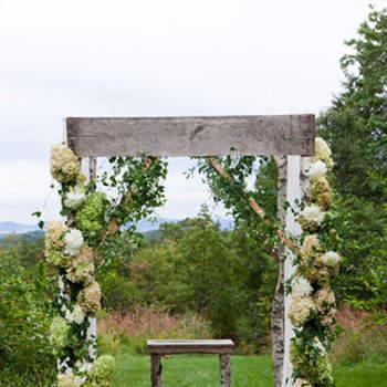 Estructura de madera con flores y telares blancos. Una opción siempre romántica!
