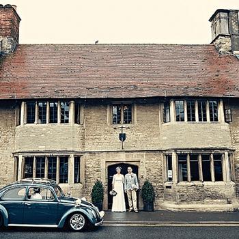 Novios posando delante de una casa.