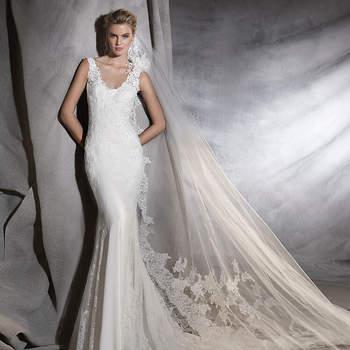 Escultural vestido de noiva de crepe e tule de corte baixo, decote em bico e estilo sereia. Um elegante modelo decorado com motivos de renda. O detalhe: uma belíssima flor numa das alças.