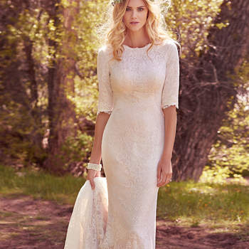 "Elegant and demure, this allover lace fit-and-flare features  elbow-length sleeves and a classic jewel neckline. Lined with Inessa jersey, and accented with a frayed scalloped hemline and back ruching. Finished with covered buttons over zipper closure.  <a href=""https://www.maggiesottero.com/maggie-sottero/mckenzie-marie/10163?utm_source=mywedding.com&amp;utm_campaign=spring17&amp;utm_medium=gallery"" target=""_blank"">Maggie Sottero</a>"