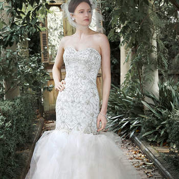 "Intricate patterns of glittering Swarovski crystals, pearls and sequins adorn the dropped bodice of this fit and flare wedding dress, with dramatic tulle skirt and sweetheart neckline. Available with optional embroidered lace cap-sleeves. Finished with crystal buttons over zipper and inner corset closure.  <a href=""http://www.maggiesottero.com/dress.aspx?style=5MT710"" target=""_blank"">Maggie Sottero</a>"