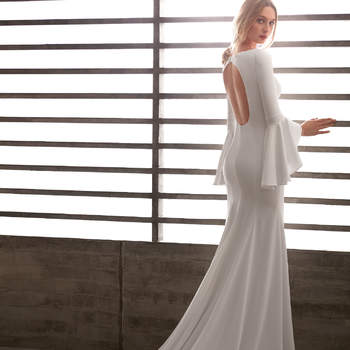 Vestido de novia con maxi volante en la manga y abertura frontal en la falda.