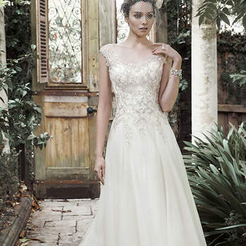"Exquisite patterns of metallic embroidered lace adorn the decadent bodice of this A-line wedding dress, complete with full tulle skirt, edged in lace. Stunning illusion cap-sleeves grace the shoulder, cascading into a scoop neckline and V-back. Finished with crystal buttons and zipper closure.  <a href=""http://www.maggiesottero.com/dress.aspx?style=5MR709"" target=""_blank"">Maggie Sottero</a>"